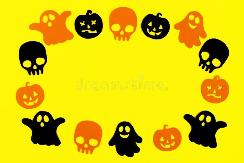 Kader van zwarte en oranje document spoken, pompoenen en schedels op een gele achtergrond Vakantiedecoratie voor Halloween royalty-vrije stock afbeeldingen