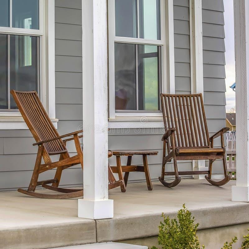 Kader Vierkante Voorportiek van een huis met bruine schommelstoelen en rechthoekige witte pijlers stock foto's