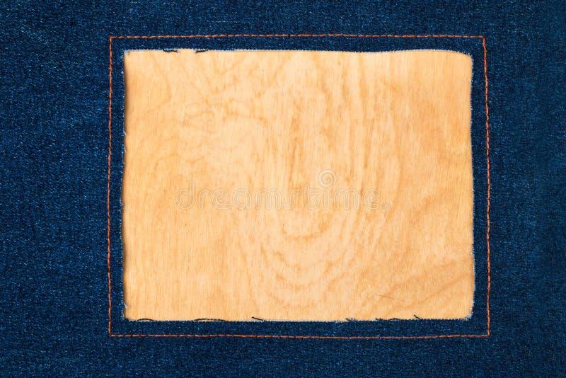 Kader voor de tekst van een donkere jeansstof met de gestikte lijnen van een oranje draad stock foto