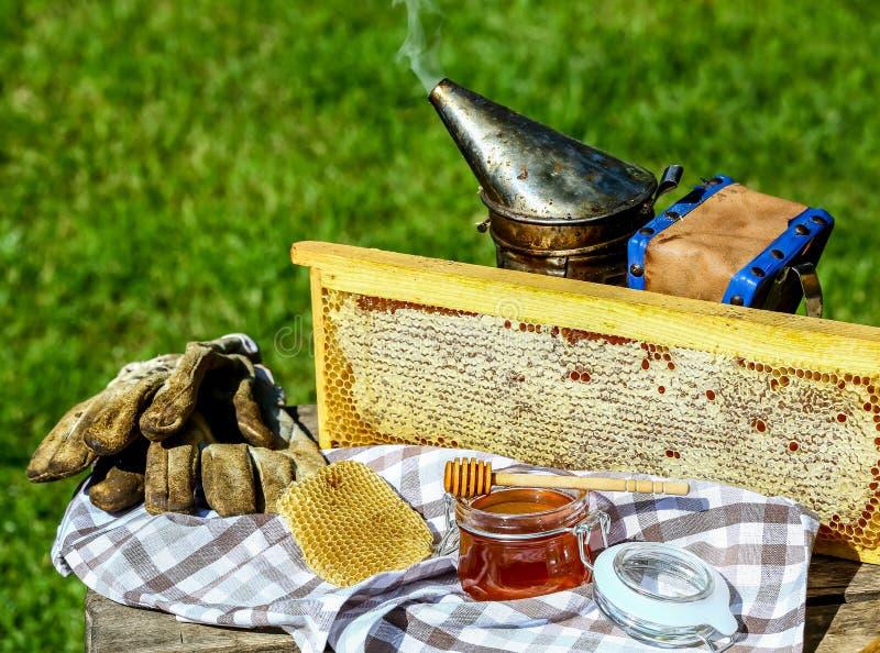 Kaderhoning hulpmiddelen voor imkerij op houten lijst Imkerijconcept royalty-vrije stock afbeeldingen