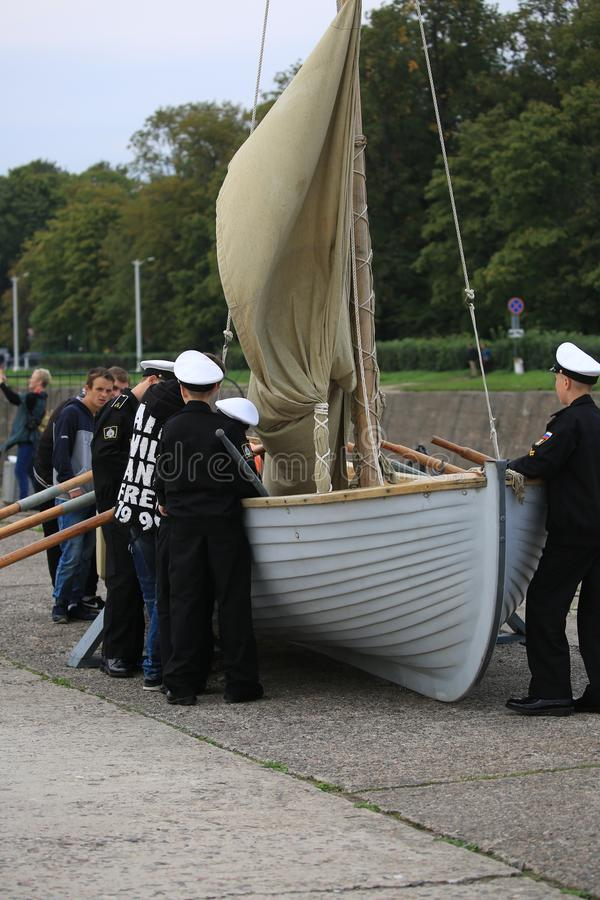 Kadetten van de zee de kadetkorpsen van Kronstadt en de burgerlijke bezoekers dichtbij de roeien-vaart boot royalty-vrije stock foto