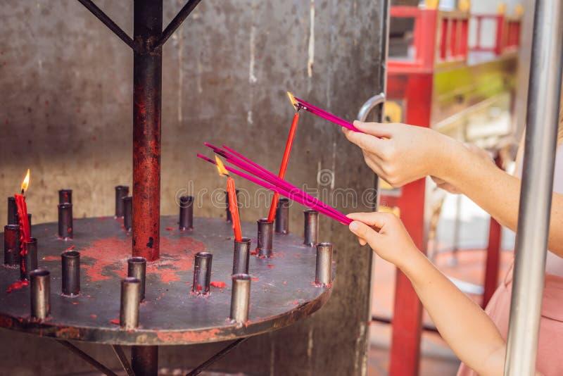 Kadzidło kije na joss kija garnku palą use dla wynagrodzenie szacuneku Buddha, dymią i Kadzą kije w, kobiety ręce u i dymu zdjęcia stock