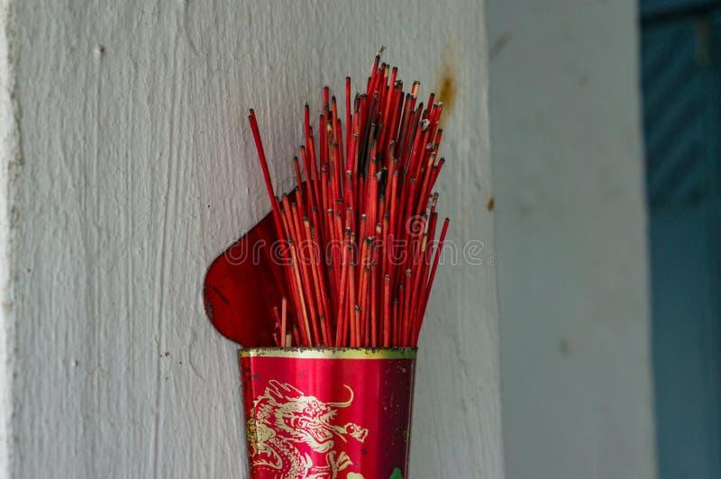 Kadzidło kije w czerwonym słoju na białej ścianie obrazy stock