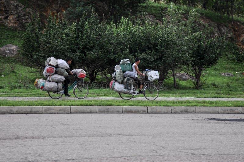 09/07/2018, Kaesong, Norden-Korea: zwei hoffnungslose überbelastete Fahrräder eln in Richtung zur Stadt rad lizenzfreies stockfoto