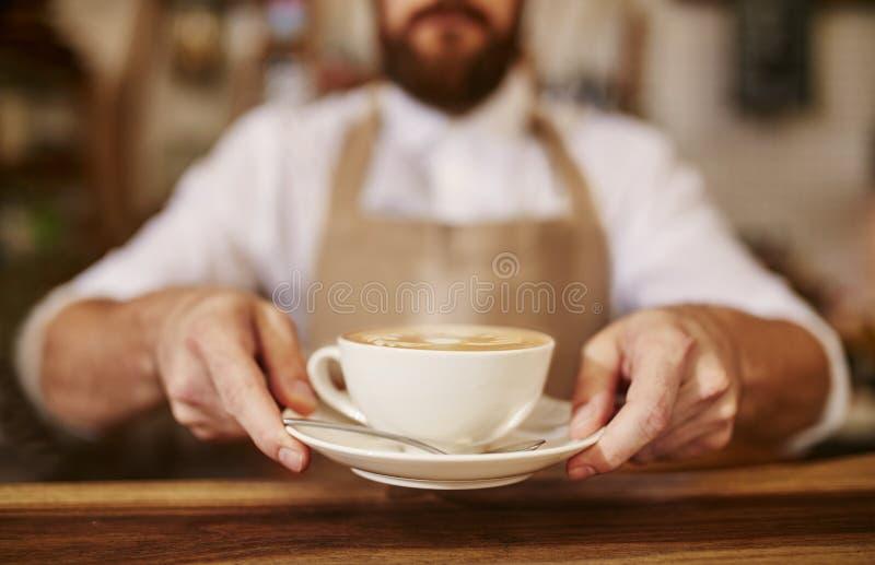 Kaféägareanseende i dörröppningen av hans coffee shop royaltyfria bilder