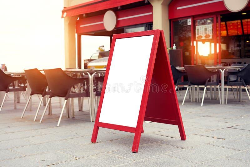 Kafé för affischtavlamenyplaceholder förutom på gatan nära restaurangterrassplatser, solnedgångljus royaltyfri fotografi