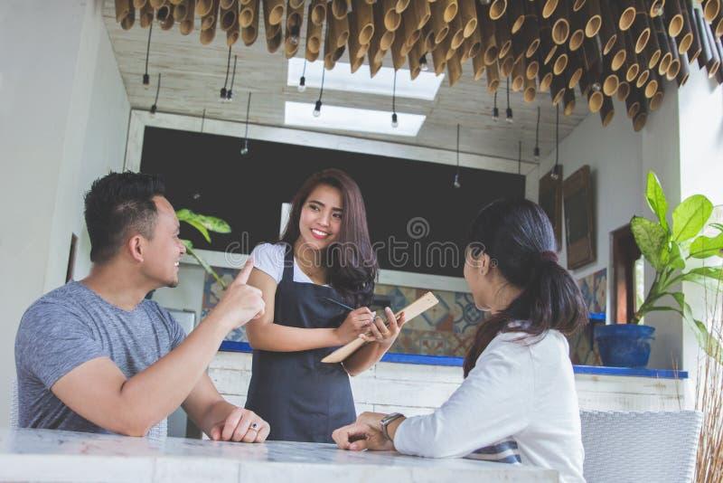 Kaféarbetare som tar en beställning från kund i coffee shop arkivbilder