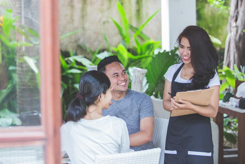 Kaféarbetare som tar en beställning från kund i coffee shop royaltyfri fotografi
