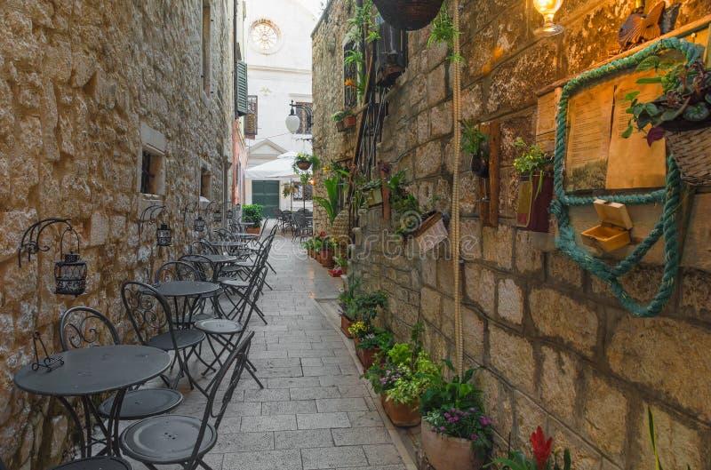 Kafét bordlägger och presiderar yttersidan i gammal hemtrevlig gata i splittring, Kroatien arkivbilder