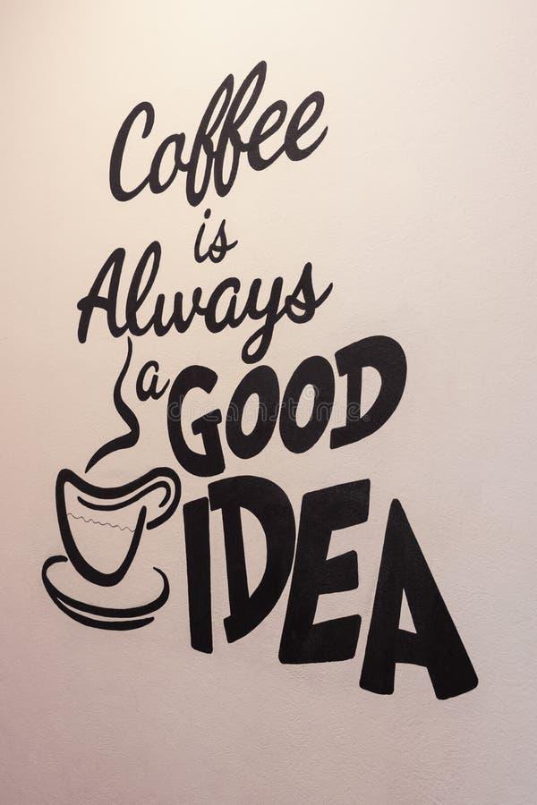 Kaffe är alltid en bra idé - det hand målade citationstecknet på en texturerad vägg arkivfoton