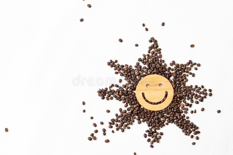 Kaffe är ett sunt och lynne-att förhöja drinken Stjärna eller sol från grillade kaffebönor med ett leende i mitt på ett vitt arkivbilder