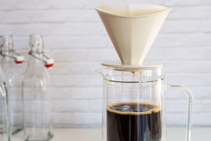 Kaffe ansträngde med kaffefiltret in i den glass kruset, hur till mor royaltyfria bilder