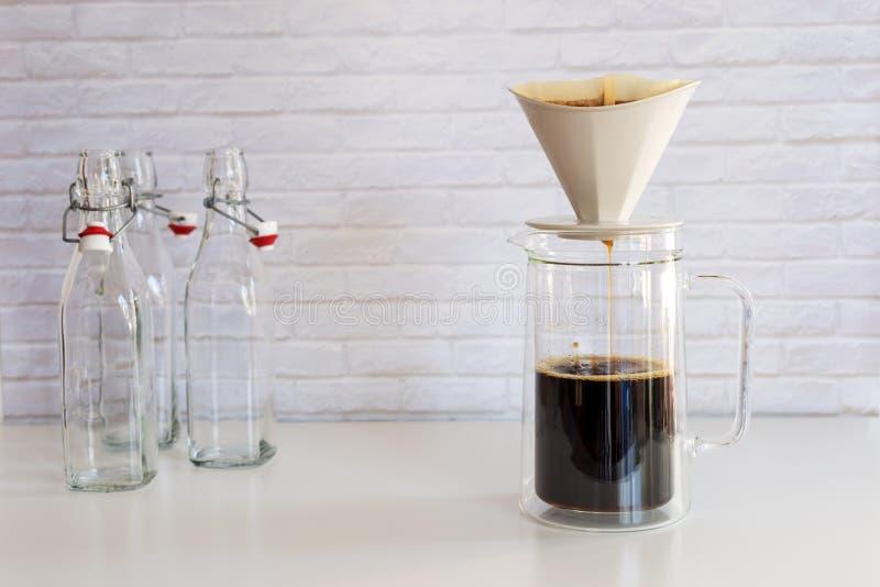 Kaffe ansträngde med kaffefiltret in i den glass kruset, hur till mor arkivbilder