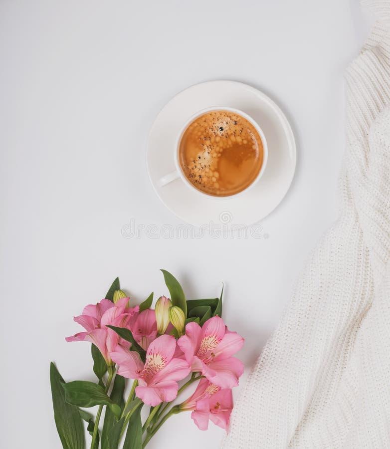 Kaffe, blommor och vitt stuckit tyg royaltyfria foton