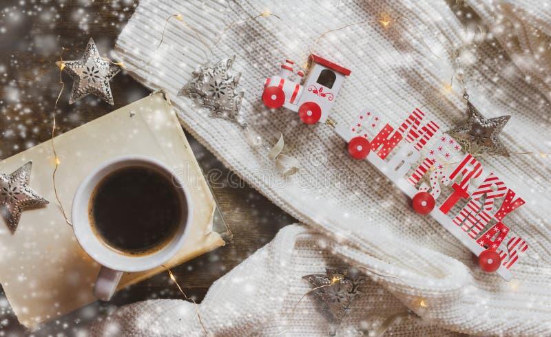 Kaffe bok, glad jul utbildar och garneringar på en träbakgrund arkivbild