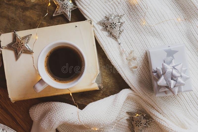 Kaffe, bok, julgåva och garneringar på en träbakgrund royaltyfri bild