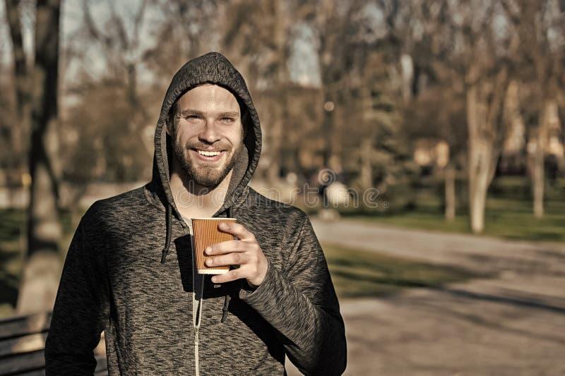 Kaffe- eller telynne Lyckligt macho i kopp för kaffe för huvhåll disponibel i soligt parkerar Skäggigt manleende med den takeaway arkivfoto