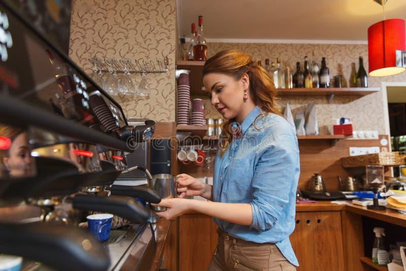 Kaffe för Barista kvinnadanande vid maskinen på kafét royaltyfria bilder