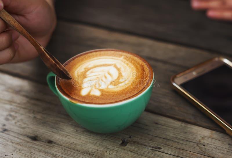 Kaffe för handmancappuccino i en grön kopp på trä royaltyfria bilder