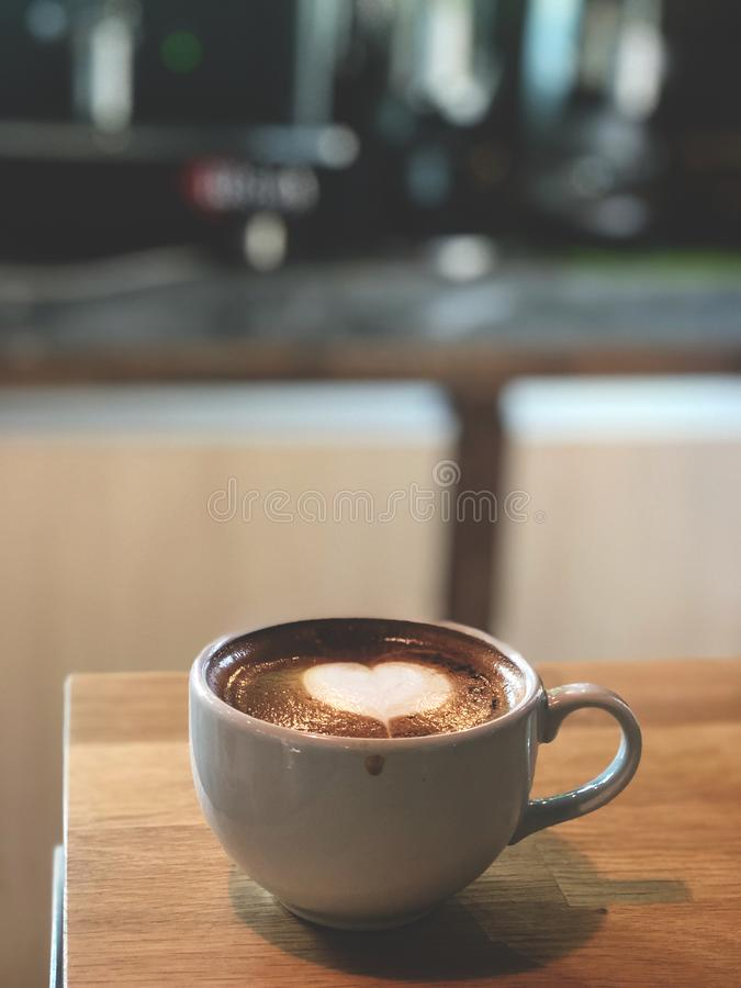 Kaffe för konst för hjärtaförälskelseLatte i den vita koppen på tappningträtabellen med kaffemaskinbakgrund arkivbilder