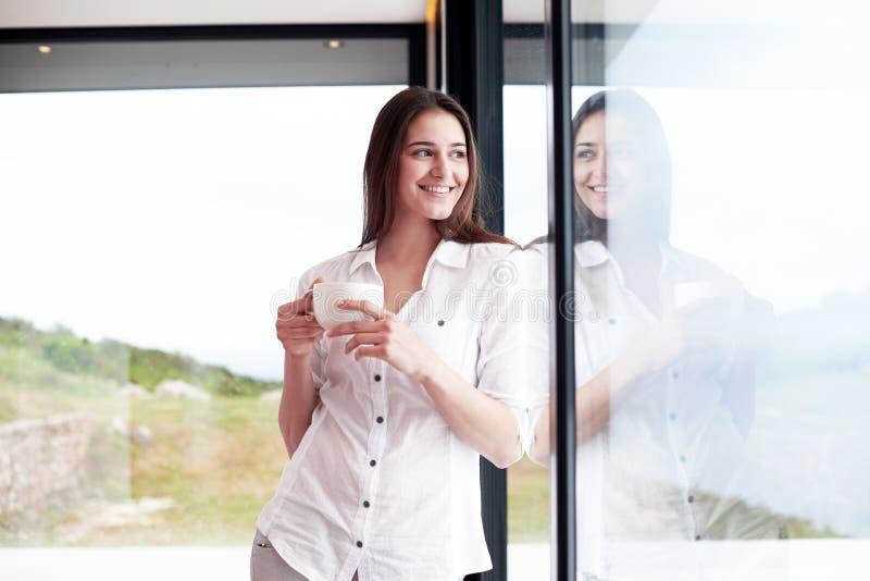 Kaffe för morgon för härlig drink för ung kvinna första royaltyfri fotografi