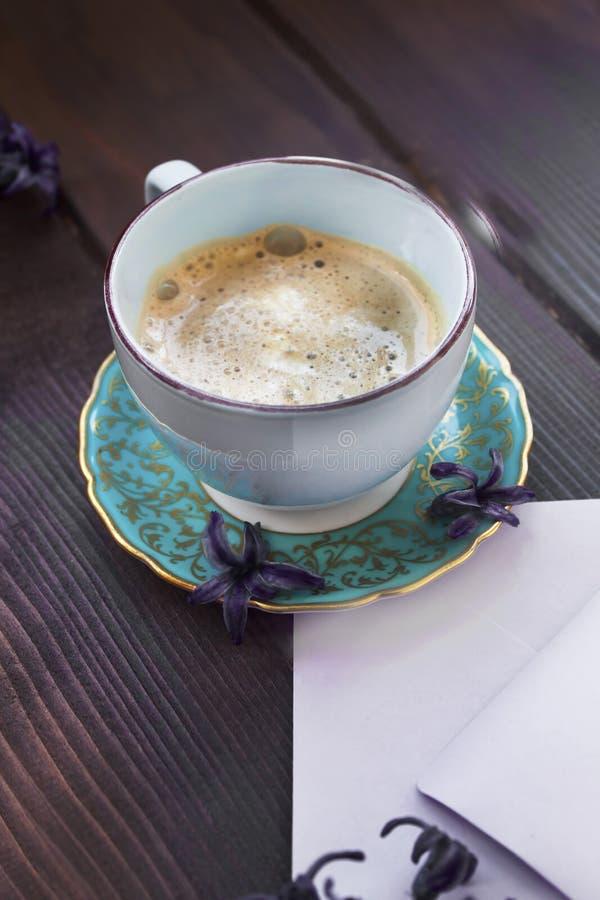 Kaffe för tappningkoppog med lila blommor arkivbild