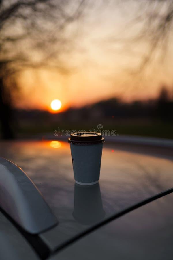 Kaffe f?r pappers- kopp p? solnedg?ngen som st?r p? ett biltak med h?rligt ut ur fokusbokeh arkivfoto