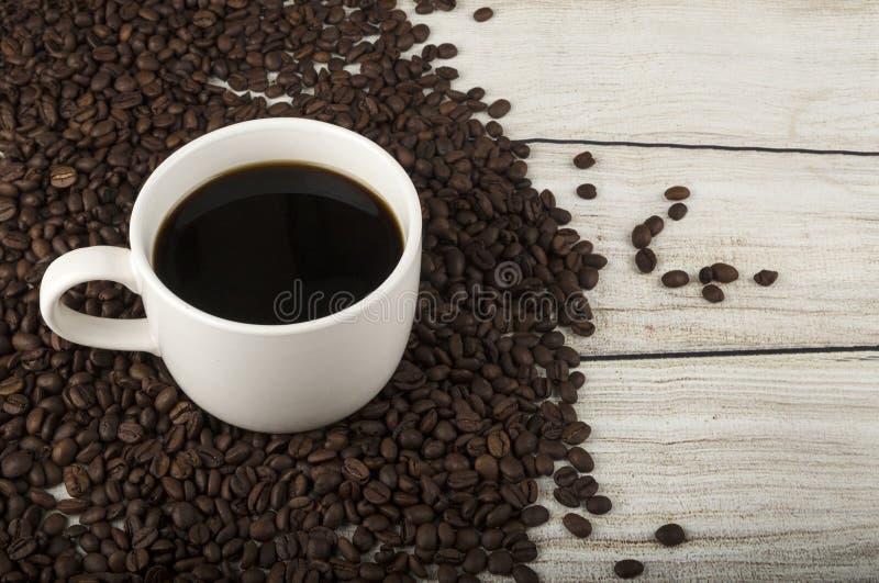 Kaffe fyllde koppen och bönor på wood bakgrund royaltyfria foton
