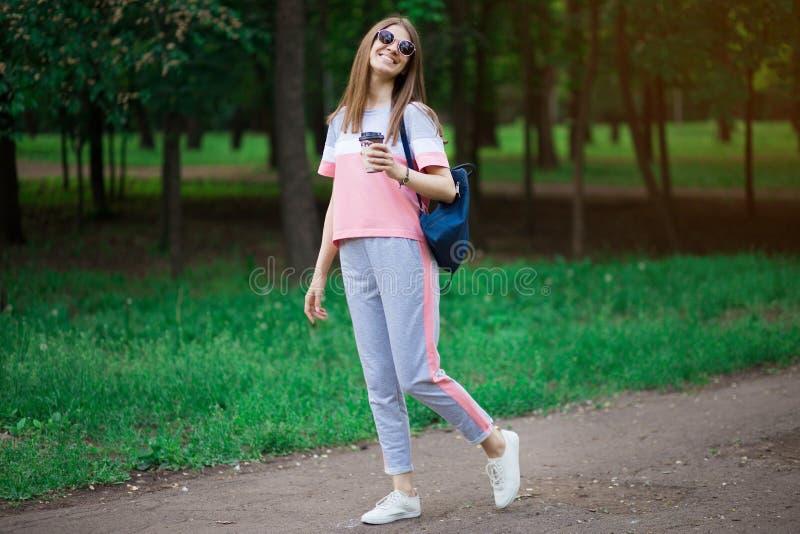 Kaffe g?r p? Härlig ung kvinna i solglasögon som rymmer kaffekoppen och ler, medan gå royaltyfria foton