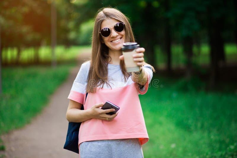 Kaffe g?r p? H?rlig ung kvinna i solglas?gon som rymmer kaffekoppen och ler, medan g? gatan royaltyfria bilder