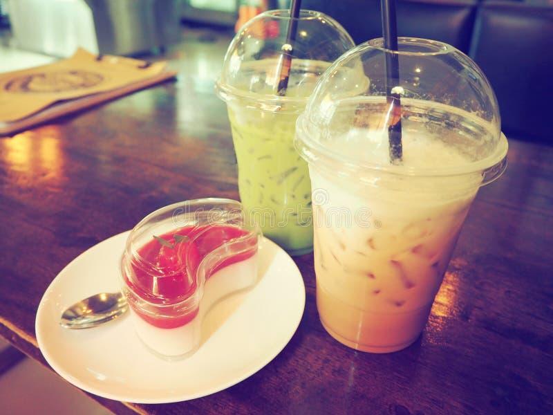 Kaffe grönt te, körsbärsröd kaka på en trätabell arkivbilder