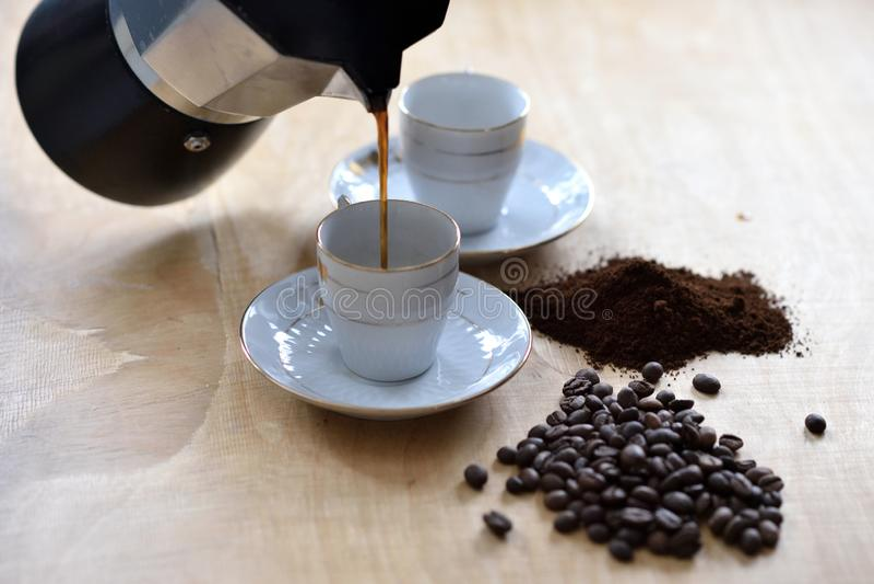 Kaffe hällde från mokakrukan för att kupa royaltyfri fotografi