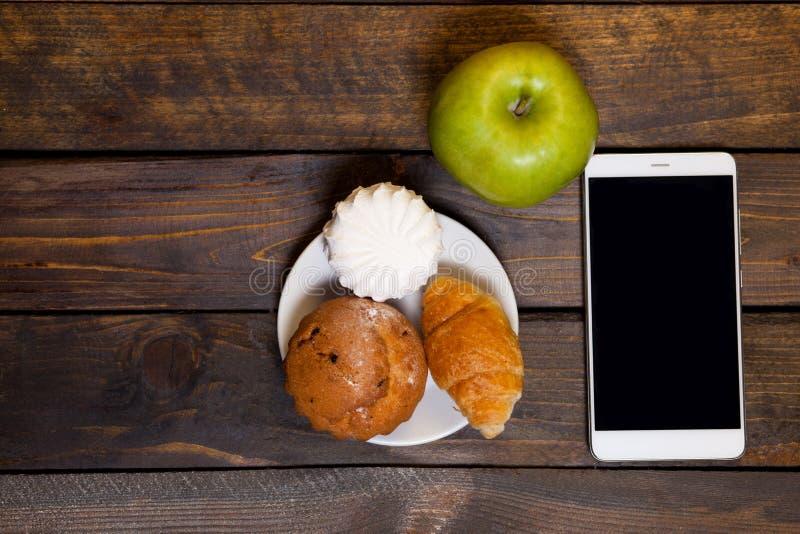 Kaffe i den vita koppen och mobiltelefonen med giffel, muffin, marshmallower och det gröna äpplet arkivbild