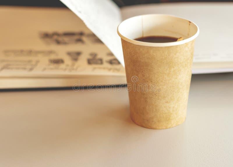 Kaffe i ett återanvändbart pappers- disponibelt exponeringsglas med en öppen anteckningsbok i bakgrund royaltyfria bilder