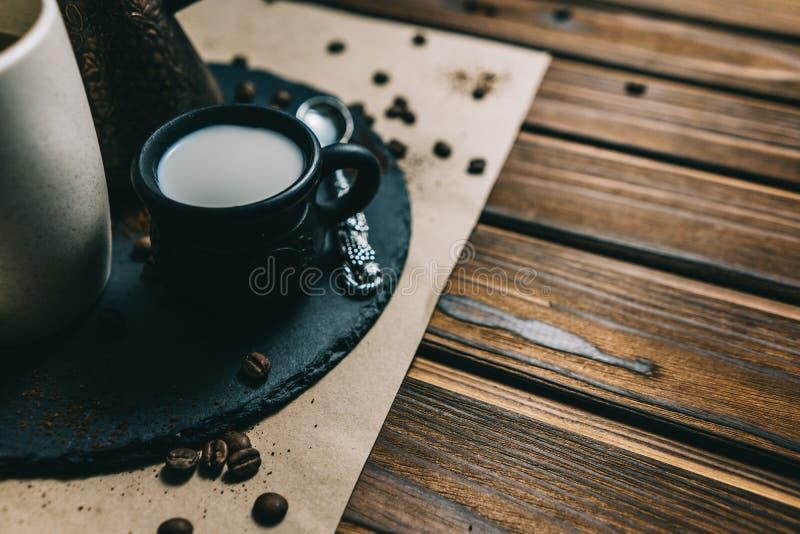 Kaffe i ett rivj?rn med en kopp p? en m?rk bakgrund med kr?m arkivfoto