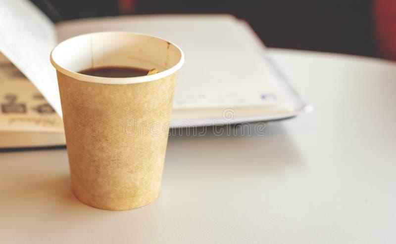 Kaffe i ett ?teranv?ndbart pappers- disponibelt exponeringsglas med en ?ppen anteckningsbok i bakgrund royaltyfri bild