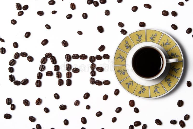 Kaffe i koppen med kaffebönor omkring royaltyfri bild