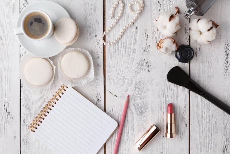 Kaffe, kakamacaron, ren anteckningsbok, glasögon och blomma på rosa färgtabellen från över Kvinnligt funktionsdugligt skrivbord H arkivfoton