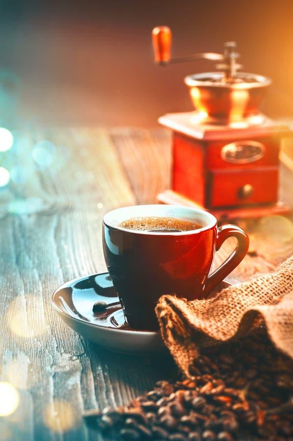 Kaffe Kopp av espresso och kaffekvarnen, grillade aromkaffebönor på trätabellen arkivfoton