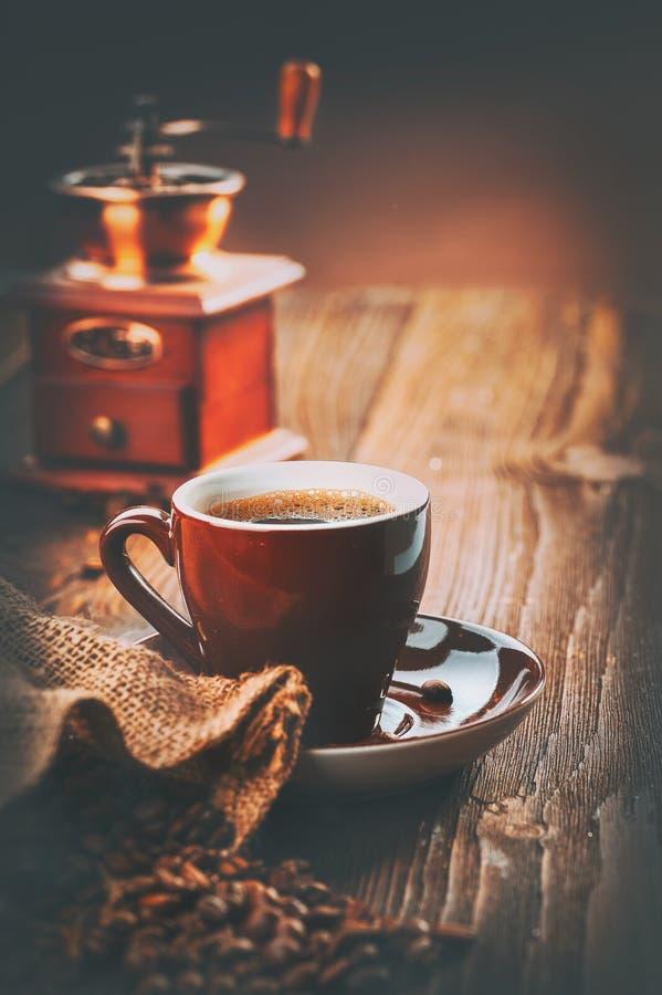 Kaffe Kopp av espresso och kaffekvarnen, grillade aromkaffebönor på trätabellen royaltyfri fotografi