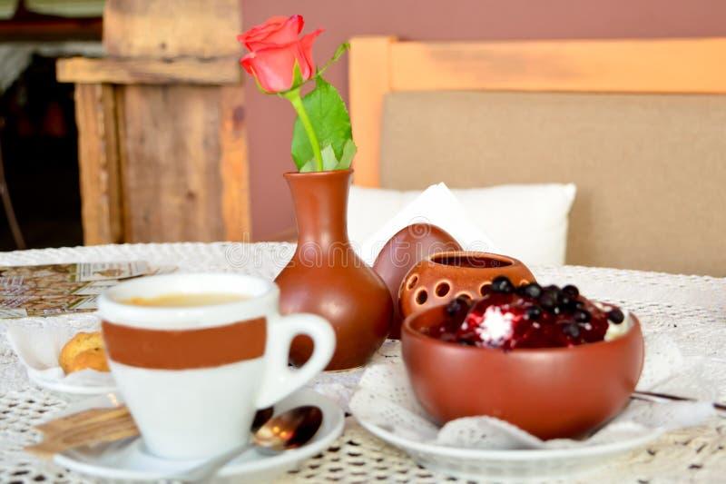 Kaffe, kopp av glass och vas med den röda rosen royaltyfria foton