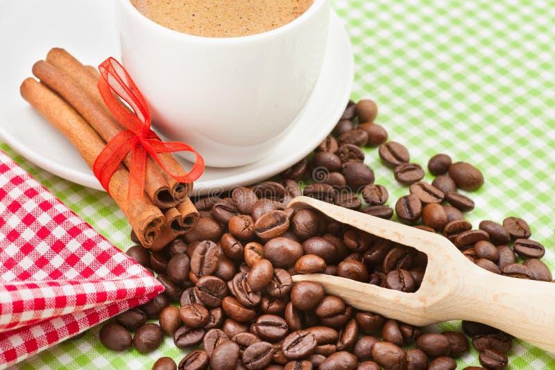 Kaffe kuper, kanelpinnar och kaffebönor royaltyfria foton