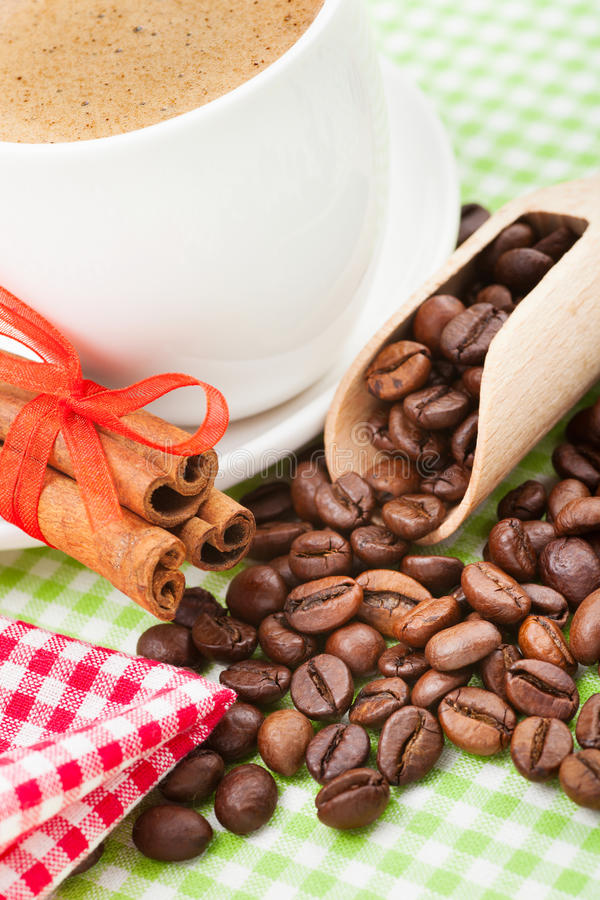 Kaffe kuper, kanelpinnar och kaffebönor arkivfoton