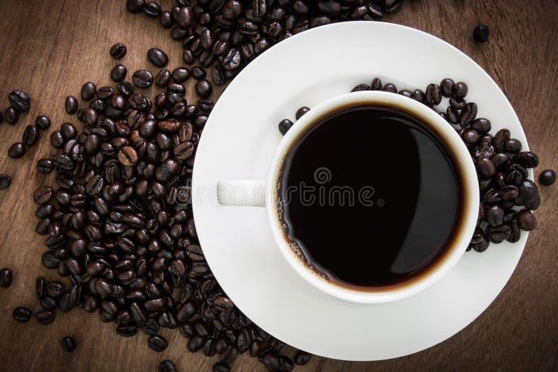 Kaffe kuper med bönor arkivfoto