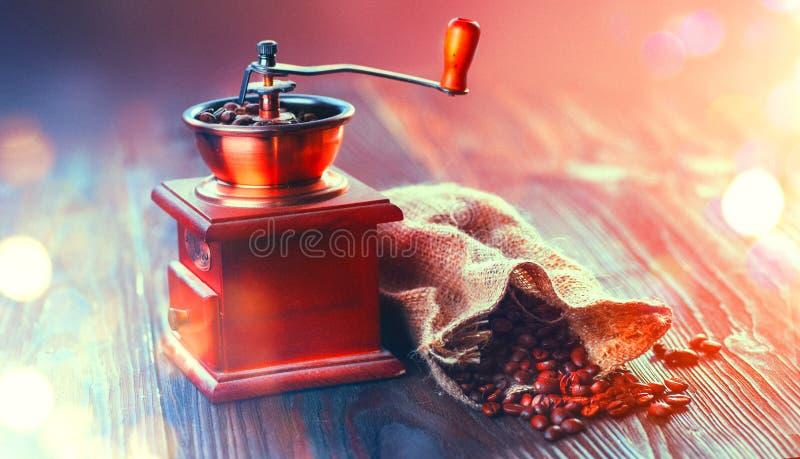 Kaffe maler och grillade kaffebönor Kaffekvarn med säckvävsäcken mycket av grillade bönor över trätabellen royaltyfri bild