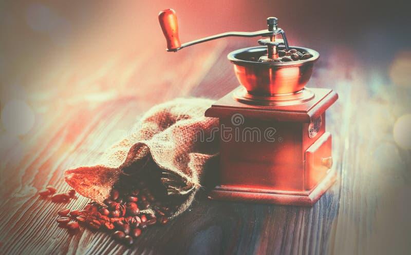 Kaffe maler och grillade kaffebönor Kaffekvarn med säckvävsäcken mycket av grillade bönor över trätabellen arkivfoto