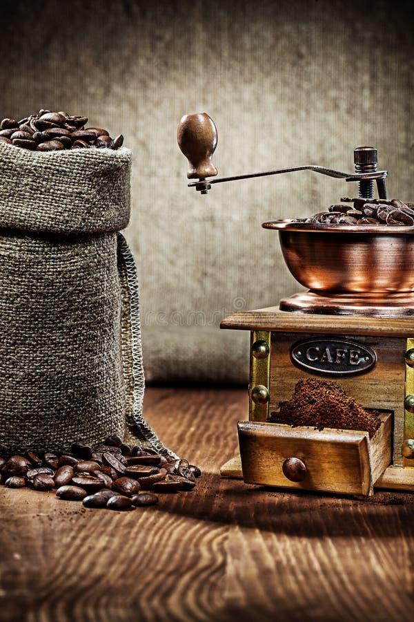 Kaffe maler och säckvävsäcken med kaffebönor royaltyfri foto