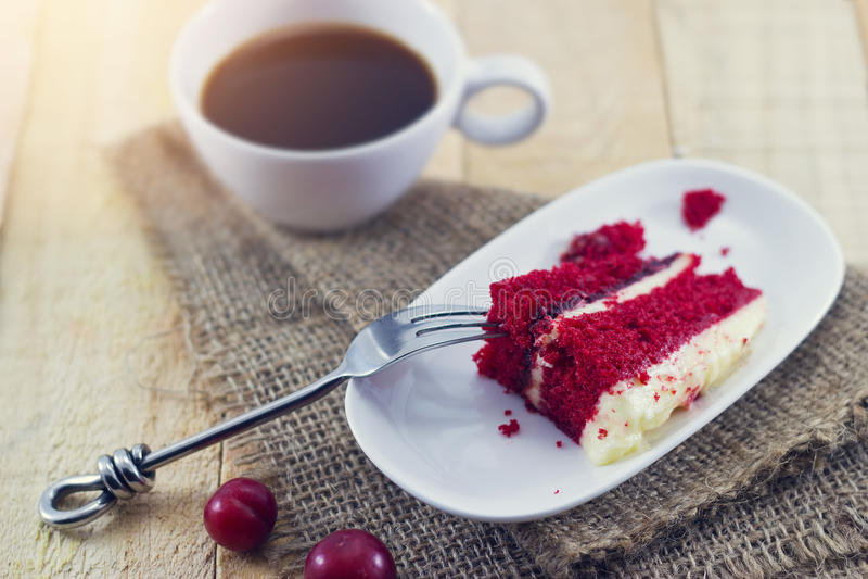 Kaffe med den körsbärsröda kakan på träbakgrund royaltyfri bild