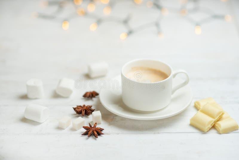 Kaffe med mjölkar, latte med kanelbruna pinnar och anisstjärnor med den vita choklad och marshmallowen, på en ljus vit bakgrund, royaltyfri fotografi