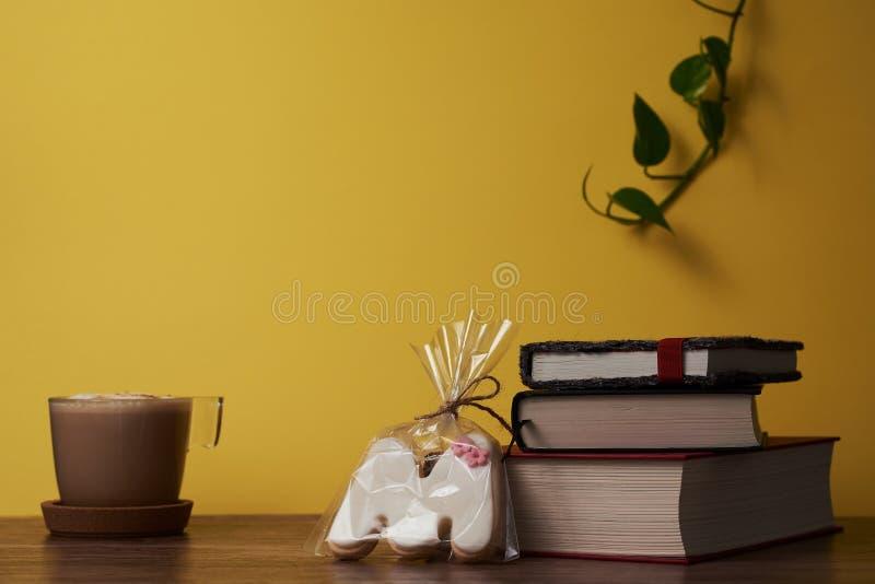 Kaffe med mjölkar och böcker på en brun trätabell royaltyfri foto